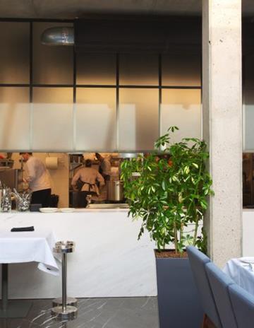 Przeszklenie w stalowej konstrukcji pomiędzy otwartą kuchnią a salą.